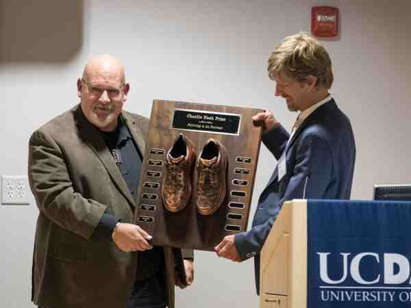 Axel Borg (left) holds the Nash Prize plaque with Flagg Miller (right), chair of the Nash Prize Selection Committee. The bronze shoes celebrate those who, like Borg, have followed in Nash's footsteps. (Photo by Fred Greaves)